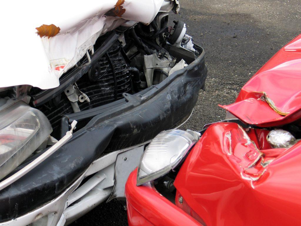 Damaged white and red car after a head on collision