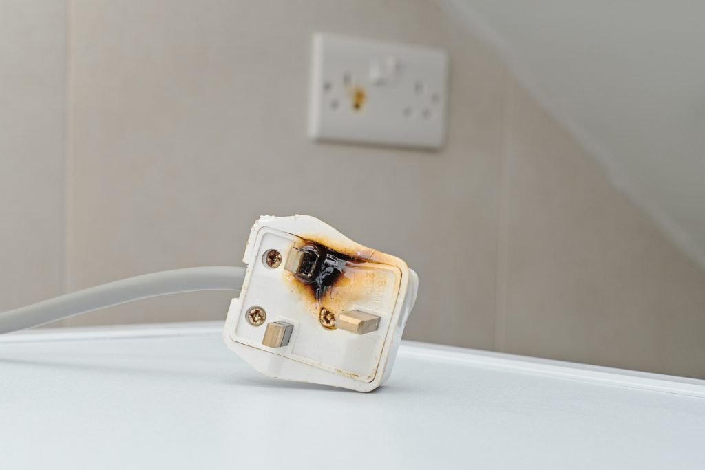 Burned AC power plug sitting in front of power outlet