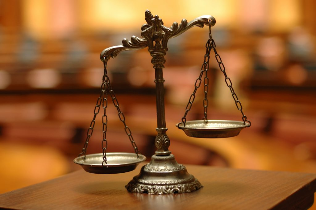 Scales of justice on a wooden table