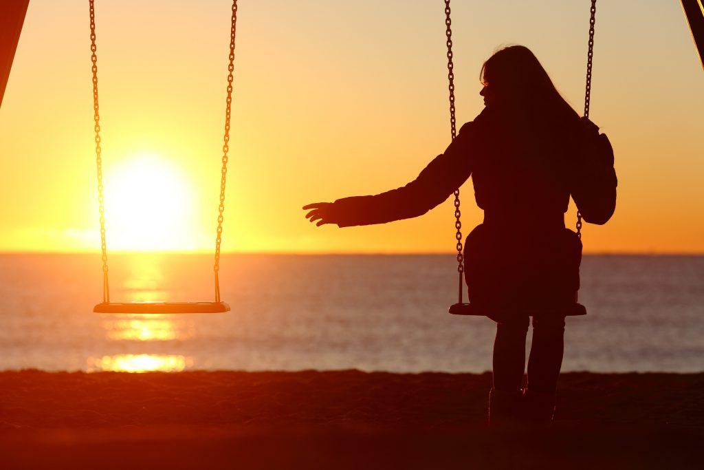 Woman sitting by an empty swing