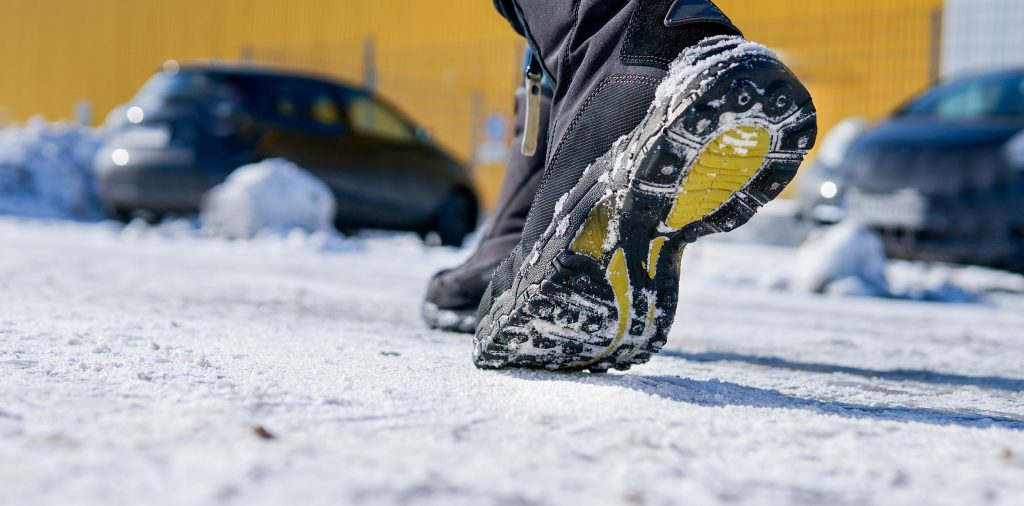 winter boots walking on an icy sidewalk