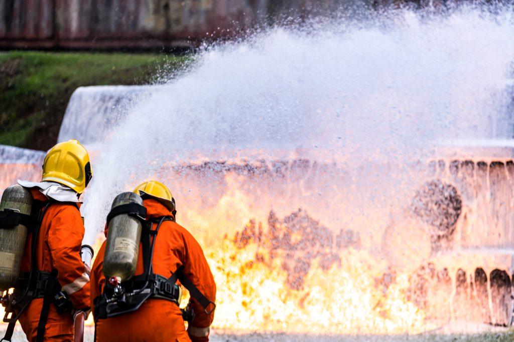 Firefighters using foam on a fire