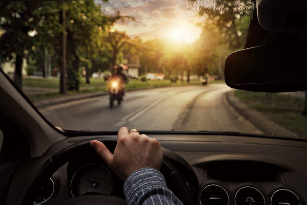 First person perspective driving a car passing a motorcycle
